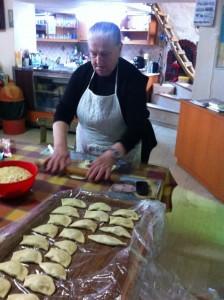 H κυρία Μαρία επί τω έργω. Με τον παραδοσιακό τρόπο πλάθει το ζυμάρι για να φτιάξει στην συνέχεια τα γευστικότατα μυζιθροπιτάκια ή χορτοπιτάκια. Το ξύλο με το οποίο πλάθει λέγεται «ξυλίκι».